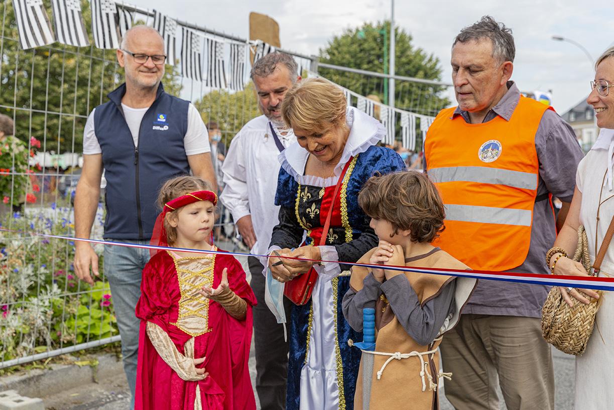 Madame la maire Elisabeth Guiheneux avec deux enfants en costume moyenâgeux, coupe le ruban pour l'inauguration du marché des enfants. Samedi 4 septembre 2021, La Guerche De Bretagne.