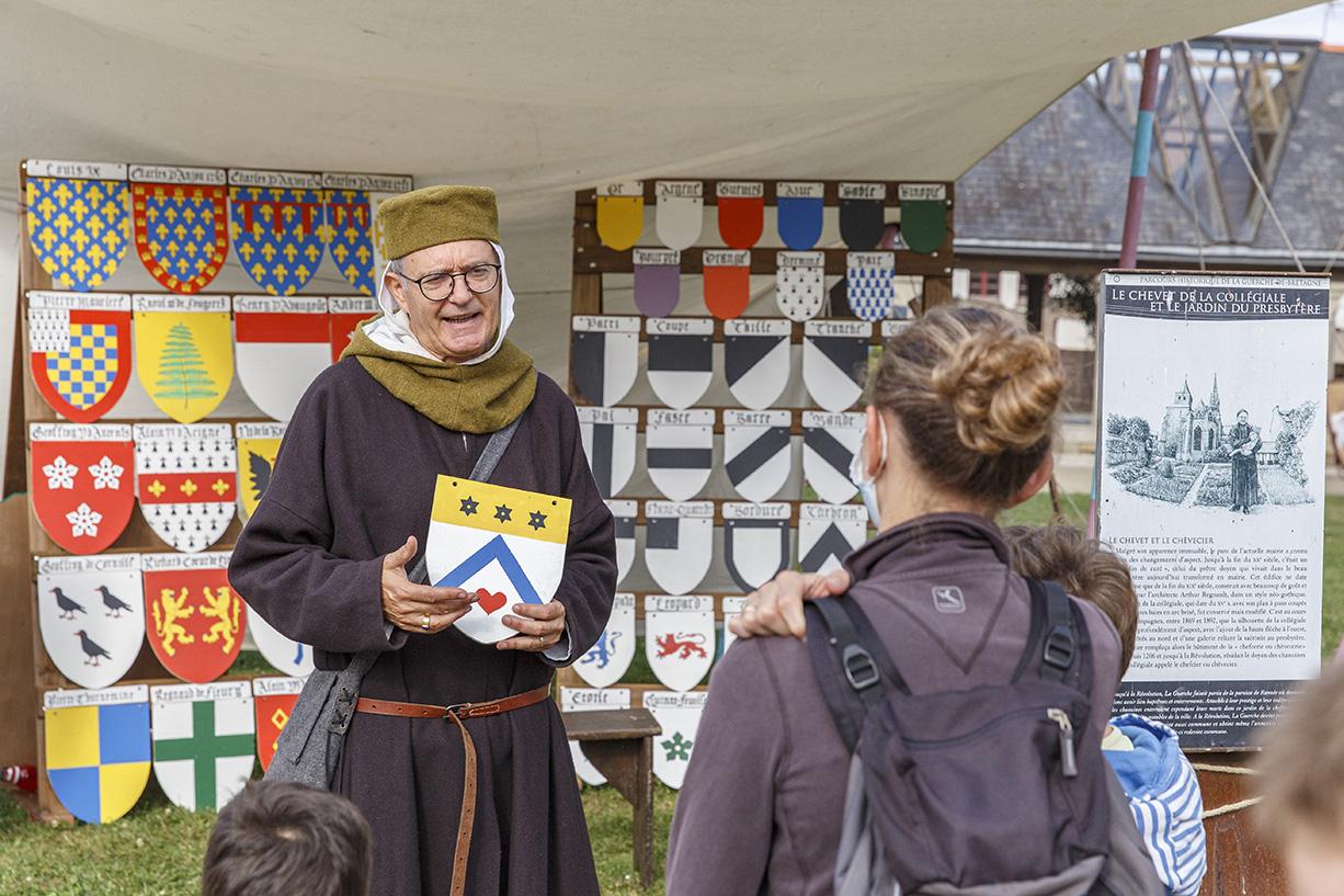 Atelier héraldique, animation médiévale dans les jardins du presbytère, avec un homme qui explique l'origine des blasons. La Guerche-de-Bretagne. Samedi 4 septembre 2021.