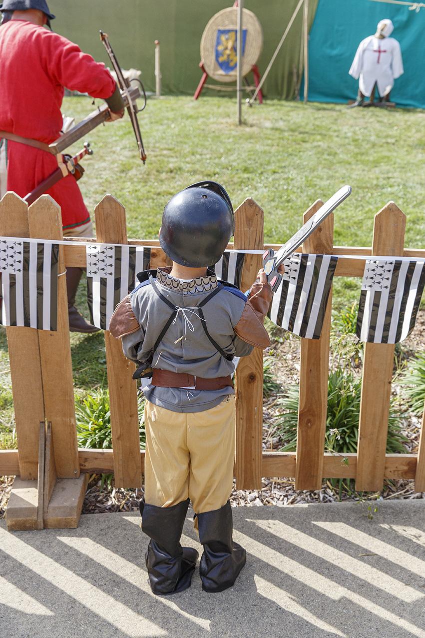 Petit garçon habillé en costume moyenâgeux, regardant une animation médiévale avec des archers durant la fête des 900 ans du marché de la Guerche-de-Bretagne. Samedi 4 septembre 2021. Petit garçon habillé en costume moyenâgeux, regardant une ani