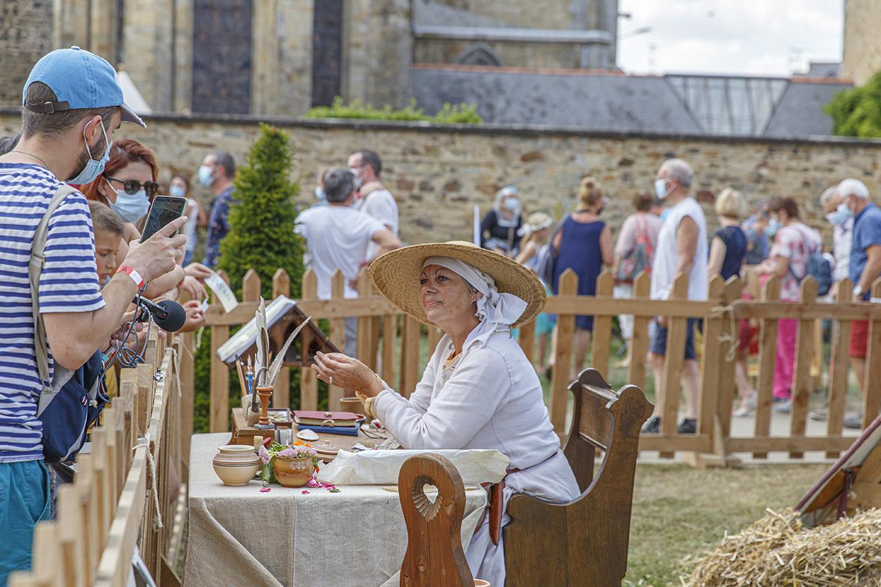 Femme qui propose de la calligraphie moyenâgeuse, au cours d'animations médiévales durant la fête des 900 ans du marché de la Guerche-de-Bretagne. Samedi 4 septembre 2021.