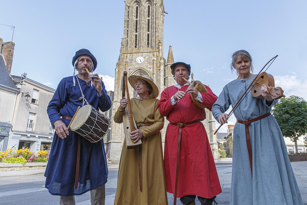 4 musiciens habillés en tenue moyenâgeuse devant la basilique, rue Notre Dame, durant la fête des 900 ans du marché de la Guerche-de-Bretagne. Samedi 4 septembre 2021.
