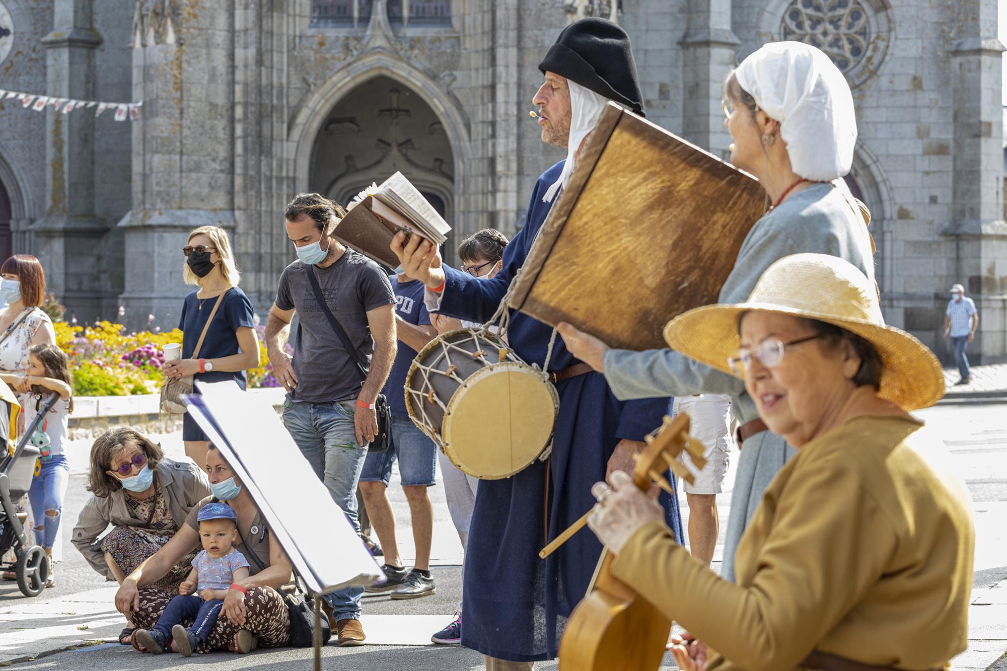 Musiciens habillés en tenue moyenâgeuse devant la basilique, avec du public en arrière plan, durant la fête des 900 ans du marché de la Guerche-de-Bretagne. Samedi 4 septembre 2021.